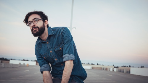 Upclose photo of young man with a beard wearing glasses