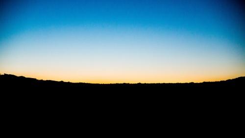 A sunset over a dark hill.