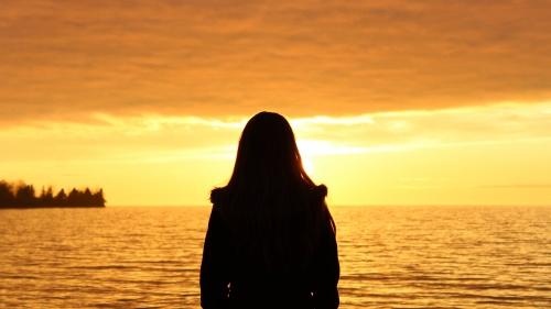 Woman standing by a body of water when the sun is setting.