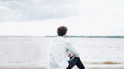 A young man sitting on the shore a lake - looking at the water.