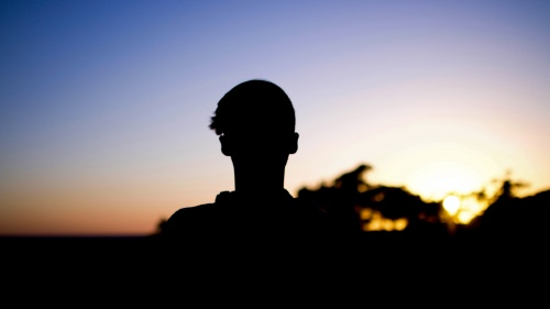 A shadow of young man looking towards the sunset.