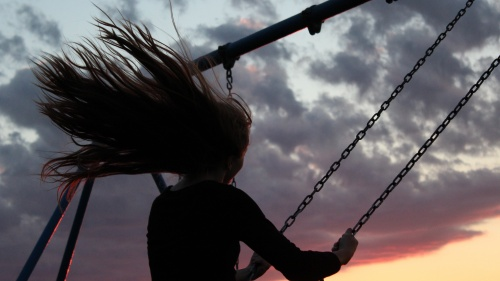 A woman swinging on a playground swing at sunset.