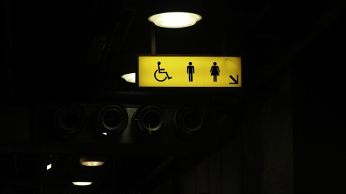 A bathroom sign with icons for a man, woman and handicap.