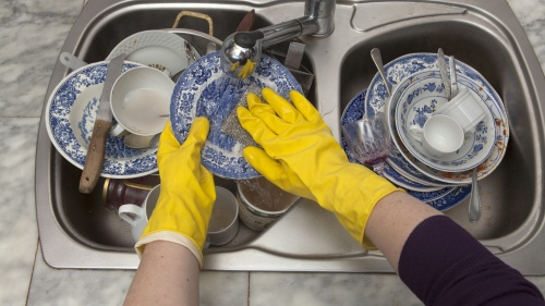 A person wearing yellow dish gloves and washing a sink full of dirty dishes.