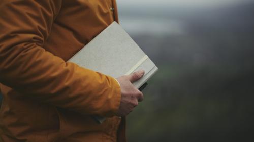 A man holding a journal notebook.