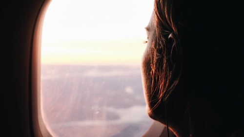 A young women looking out the window of an airplane.