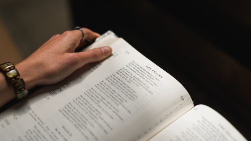 A woman holding a Bible opened to the Psalms.
