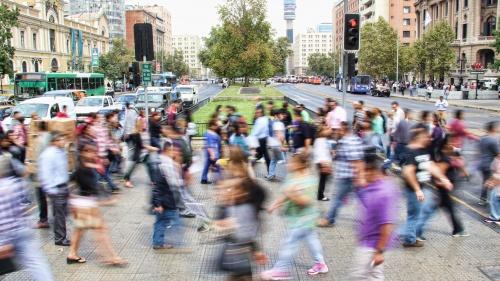 A blur of crowded city sidewalk of people walking.