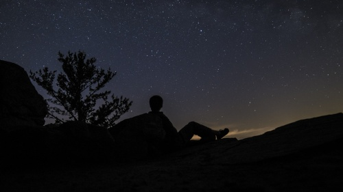 A person looking up at the millions of stars filling the night sky.