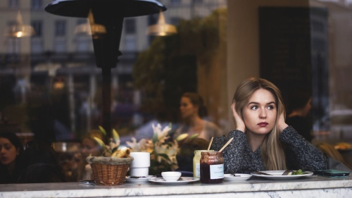 A young woman sitting at restaurant counter looking out the front window.