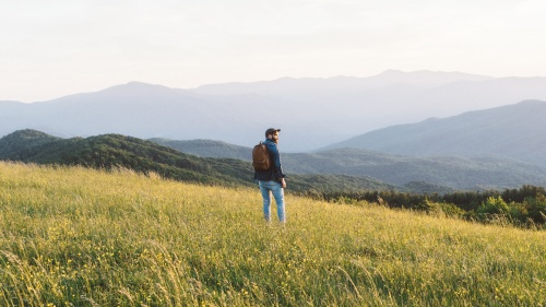 A man hiking in field with mountains in the background.