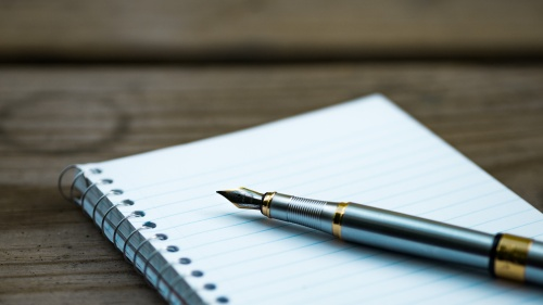 A writing pen on top of spiral bound notebook.