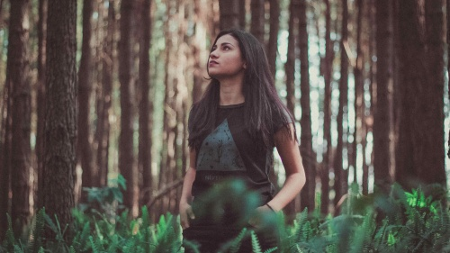 A young woman staring up while standing in tall grass near trees.