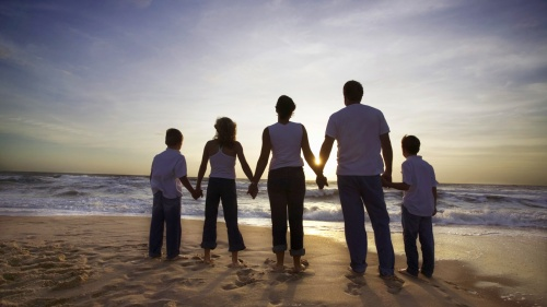 A family holding hands looking at the ocean waves and the sun setting.