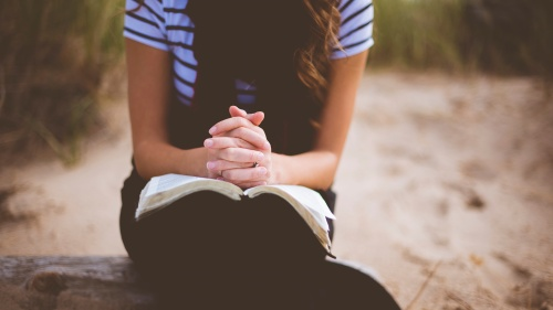 A young women with her hands clasped resting on top of a Bible.