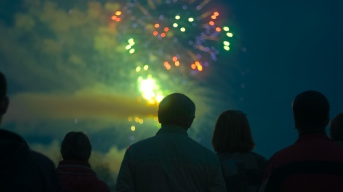 People watching the night sky filled with fireworks.