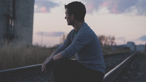 A young man sitting by an old railroad track.