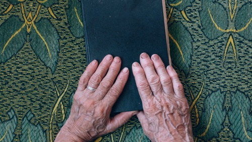 An older woman's hands resting on top of a Bible.