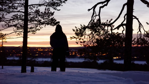 A person standing in the snow looking out over a town.