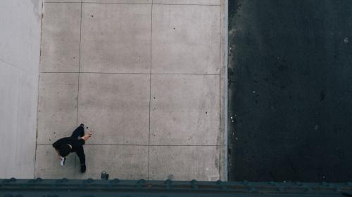 A man walking alone on a sidewalk.