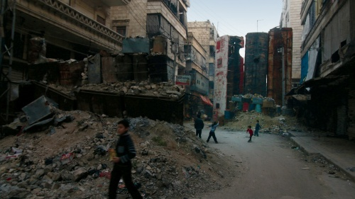 Children play in the bombed out rubble of their homes behind a sniper screen made of buses in Aleppo, Syria.