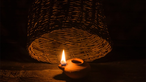 A basket almost covering the light of a small oil lamp.