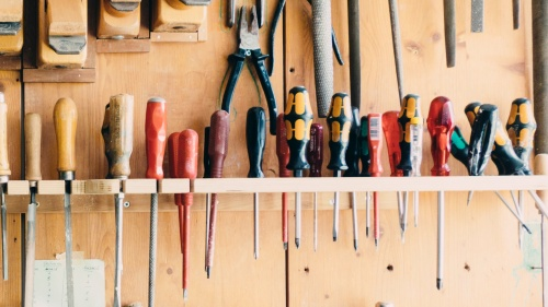 A workbench wall with many types of screwdrivers hanging.