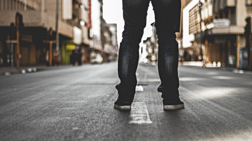 A person standing in the middle of a road.