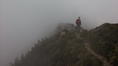 A person hiking on a narrow mountain path surrounded by fog.