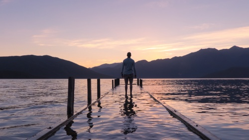 A man standing on a dock covered by water.