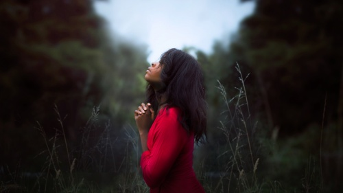 A young woman praying in a field.