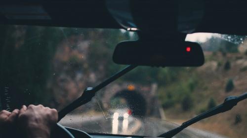 A man driving a car in the rain.