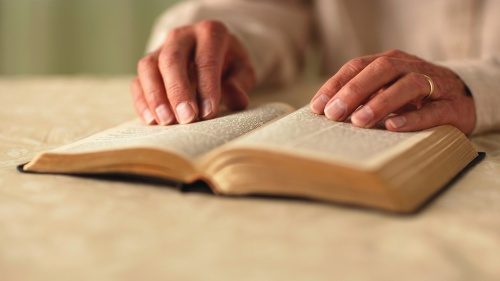 A woman turning the pages of a Bible.