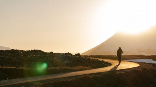 A person walking on a narrow road with the sun setting in the background.