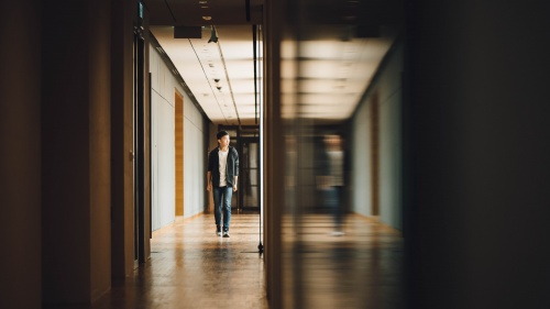 A young guy walking in the hallway of a building.
