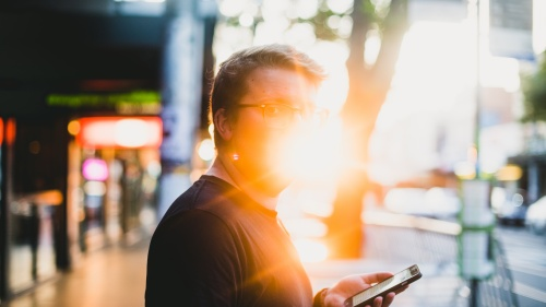 A man holding a smartphone with the sun glaring behind him.