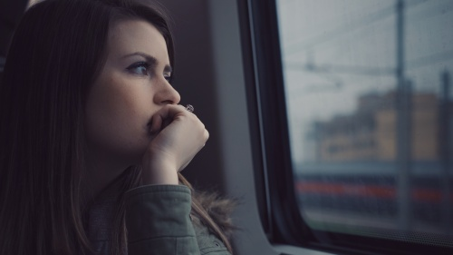 A woman looking out of a window on a commuter train.