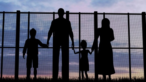 A family of four looking through a tall fence.