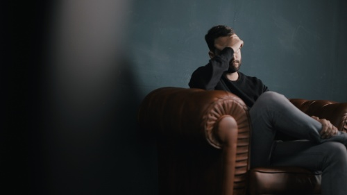 A man sitting on a chair holding his head with his hand.