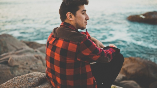 A young man sitting on a rock looking out over the water.