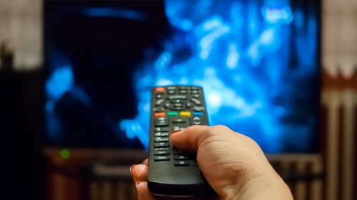 A woman's hand pointing a TV remote control at a television.