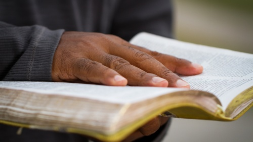 A man holding an open Bible.