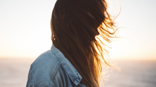 Sun rays shining through a young woman's hair.