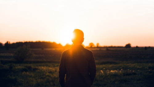 A young person watching a sunset.