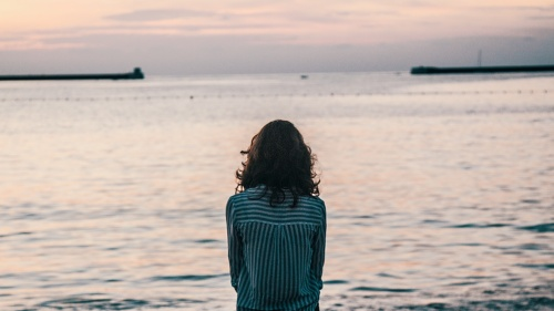 A woman sitting by a large body of water.