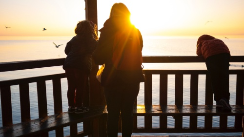 A mom with children on a deck looking over water.