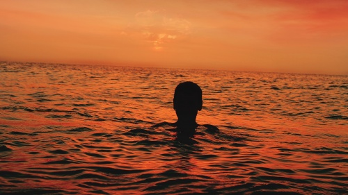 A person floating in the water with the sun setting.