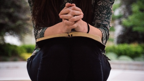 A woman with her clasped in prayer on top of an open Bible.