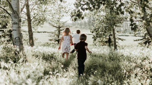 Three kids running through a field.