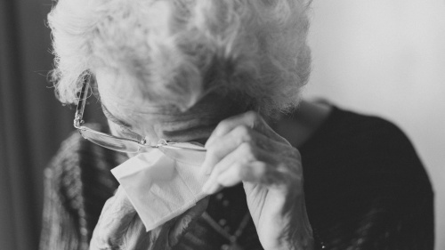 An elderly lady wiping her eyes.